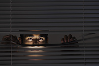 Young man looking through blinds with just his eyes visible - Alex Mares-Manton