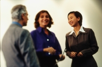 Asian female executive talking with two Caucasian executives - Keith Brofsky