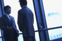 Two male executives talking in airport, silhouette - Keith Brofsky