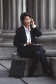 Female executive sitting, using cellular phone - Alex Microstock02