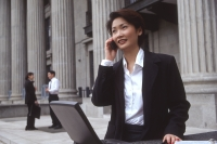 Female executive with laptop computer and cellular phone - Alex Microstock02