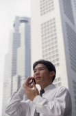 Male executive talking on cellular phone with office buildings behind, low angle view - Alex Microstock02