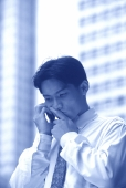 Male executive using cellular phone, thoughtful expression - Alex Mares-Manton