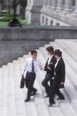 Three executives walking down a flight of steps - Alex Microstock02