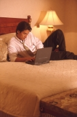Male executive in hotel room using laptop computer - Alex Microstock02