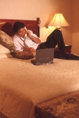 Male executive in hotel room talking on phone, with laptop computer - Alex Microstock02