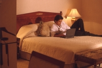 Male executive in hotel room working on laptop computer - Alex Microstock02