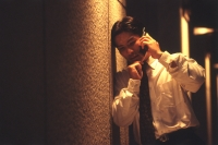 Male executive talking on cellular phone under street lamp at night - Alex Microstock02
