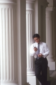 Male executive looking at cellular phone, pillars behind - Alex Microstock02