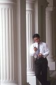 Male executive looking at cellular phone, pillars behind - Alex Microstock02