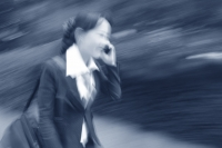 Female executive talking on cellular phone (motion blur) - Alex Mares-Manton
