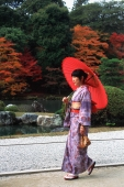 Japan, woman in kimono walking in temple garden with red umbrella - Rex Butcher