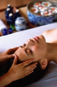 Eurasian female lying down receiving a head massage - John McDermott