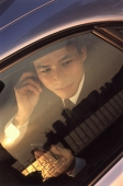 Male executive using cellular phone, sunset reflected in car window - Jade Lee