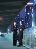Two executives talking at night, skyline behind - Jade Lee
