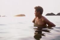 Young man standing in ocean, looking at horizon - Jade Lee