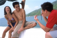Teenage couple in swimwear posing for photo on deck of boat - Jade Lee
