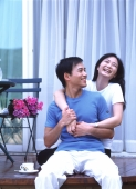 Couple sitting on balcony, embracing and laughing - Jade Lee