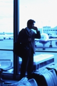 Male executive talking on cellular phone in airport lounge - Keith Brofsky