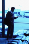 Male executive holding cellular phone in airport lounge - Keith Brofsky