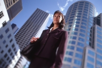 Female executive standing in front of high-rise buildings, low angle view - Keith Brofsky