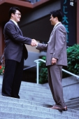 Two male executives shaking hands on stairway - Keith Brofsky