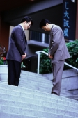 Two male executives bowing on stairway - Keith Brofsky