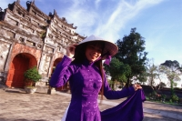 Vietnam, Hue, the Citadel,  woman in traditional Vietnamese dress - John McDermott