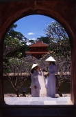 Vietnam, Hue, Tomb of Minh Mang, two young women in traditional Vietnamese dress - John McDermott