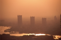 Thailand, Bangkok, Condominiums seen through the smog across the Chao Praya River - John McDermott