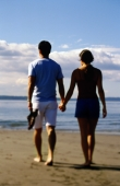 Young couple hand-in-hand, walking on beach (rear view) - Keith Brofsky