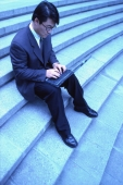 Male executive sitting on steps, using laptop - Keith Brofsky