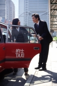 Female executive getting into taxi, male executive holding door - Gareth Brown