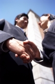Two executives shaking hands, low angle view - Gareth Brown