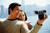 Couple by waterfront, man holding video camera - Gareth Brown