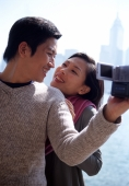 Couple looking at each other by waterfront, man holding video camera - Gareth Brown