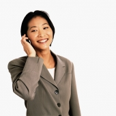 Female executive talking on cellular phone, white background - Gareth Brown