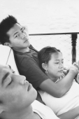 Teenagers relaxing on deck of boat - Jade Lee