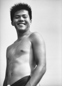 Teenage boy in swimsuit smiling, portrait, low angle view - Jade Lee