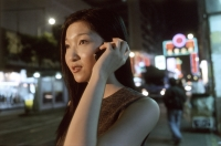 Female executive talking on cellular phone with neon in background - Jade Lee