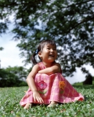Girl sitting on grass laughing, tree in background - Alex Microstock02