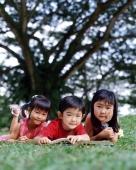 Three children lying down on grass reading a book - Alex Microstock02