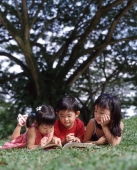 Three children lying on grass reading book - Alex Microstock02