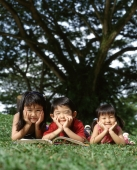 Three children lying down on grass with a book - Alex Microstock02