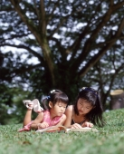 Two children lying on grass reading a book - Alex Microstock02