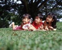 Three children lying on grass reading a book - Alex Microstock02