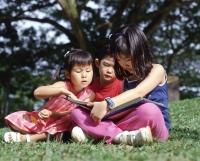 Three children sitting on grass reading a book - Alex Microstock02