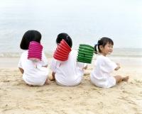 Three children sitting on the beach holding chinese lanterns, rear view - Alex Microstock02