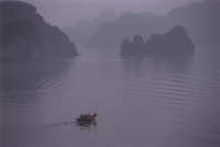 Vietnam, Halong Bay, lone fishing boat in the mist. - Steve Raymer
