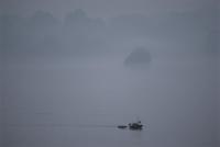 Vietnam, Halong Bay, lone boat in the mist. - Steve Raymer